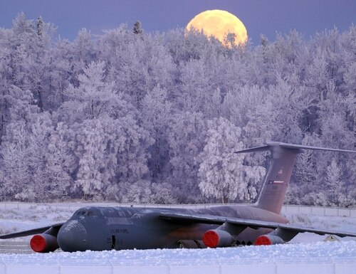 The waning, gibbous moon is seen above a U.S. Air Force C-5 Galaxy transport aircraft on the flight line at Joint Base Elmendorf-Richardson, Alaska as hoarfrost engulfs nearby trees in -16F weather while airmen work around the plane. (Justin Connaher/Air Force)