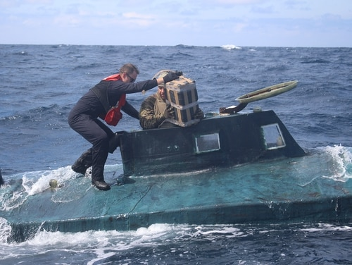 U.S. Coast Guard boarding team members climb aboard a suspected smuggling vessel in September. The 40-foot self-propelled semi-submersible vessel carried an estimated 12,000 pounds of cocaine, plus four suspected drug smugglers. (Coast Guard)