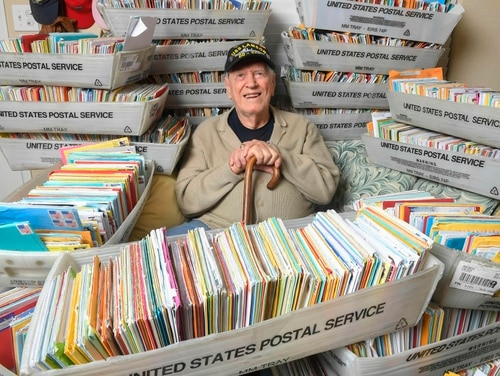 Duane Sherman, 96, with a small fraction of the 50,000 birthday cards he received after his daughter's social media request for people to send him cards to cheer him up on his birthday went viral. (Kevin Sullivan/Orange County Register via AP)