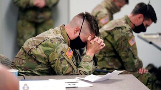 Minnesota National Guard chaplains bow during a prayer after a time of devotion Oct. 19, 2020 in St. Paul, Minn. (AP Photo/Jim Mone)
