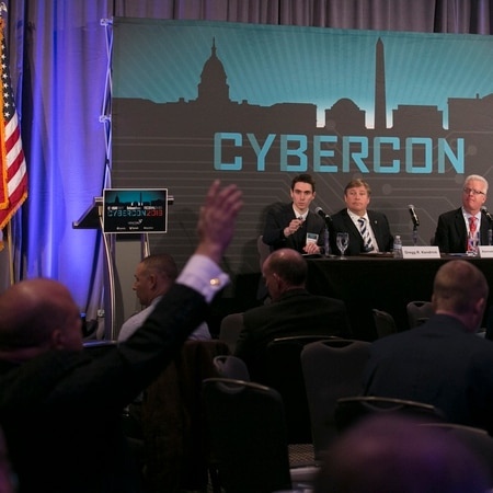 A man asks a question during a panel at Cybercon 2016. (Daniel Woolfolk/Staff)