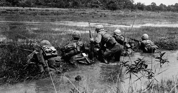 An American Army combat platoon leader, 2nd Lt. John Libs, surveys the situation with his men from the relative safety of a watery rice paddy as they prepare to advance on a Viet Cong sniper position, Vietnam, in the mid-1960s. (Hulton Archive/Getty Images)