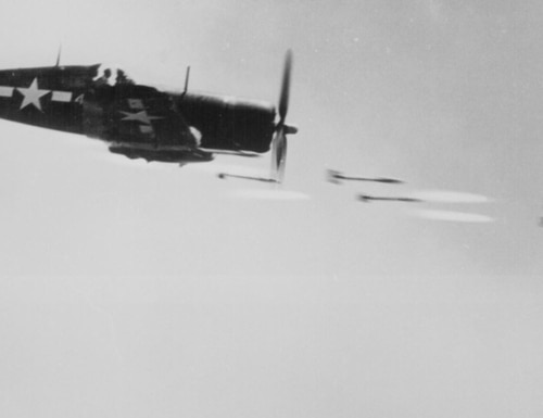 A Corsair fighter fires rocket projectiles at a Japanese stronghold on Okinawa, ca. June 1945. The Navy test pilot who helped to perfect the plane, and dozens of other aircraft, was the legendary Frederick