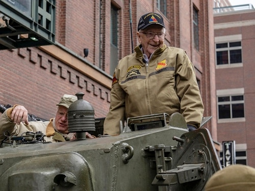 In this March 30, 2019, photo, Cpl. Clarence Smoyer settles into a tank as volunteer historical re-enactors roll through lower downtown Denver as part of a ceremony to honor Smoyer, who served with Gen. Maurice Rose of Denver in World War II. (Eric Lubbers/The Colorado Sun via AP)