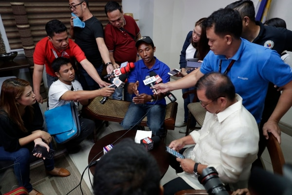 Reporters interview a crew of Filipino fishing vessel F/B Gimver 1, Richard Blaza, center, during a press conference at the Department of Agriculture in metropolitan Manila, Philippines on Monday. (Aaron Favila/AP)