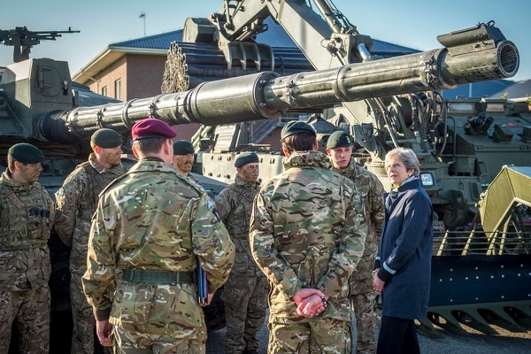 British Prime Minister Theresa May, right, speaks to a group of soldiers of the NATO Battle Group at the Tapa military base in Estonia on Sept. 29, 2017. She was guaranteeing Britain's security commitment to the other 27 European Union leaders. (Marko Mumm/AP)