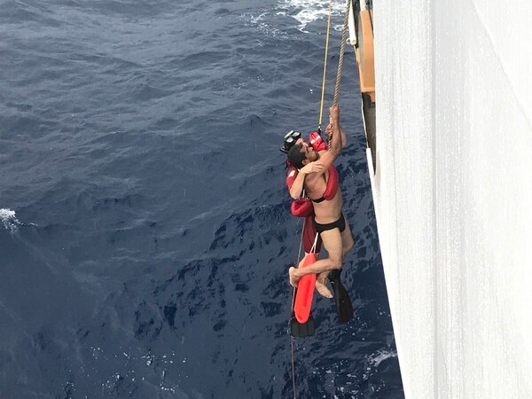 A Coast Guard rescue swimmer holds onto a crew member from the Ecuadorian fishing vessel Marujita as they are hoisted onto an unidentified cutter on Wednesday. (Coast Guard)