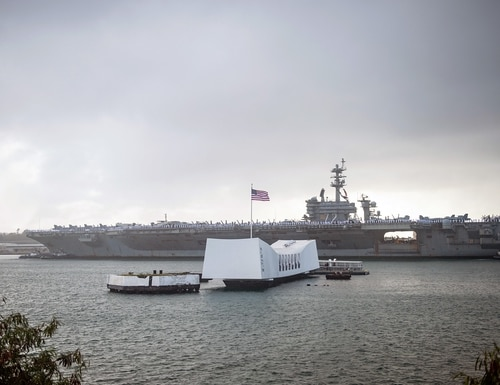 The aircraft carrier Abraham Lincoln passes the USS Arizona Memorial on Jan. 8 as it arrives at Joint Base Pearl Harbor-Hickam as part of an around-the-world deployment that includes a homeport shift to San Diego. (Mass Communication Specialist 2nd Class Cole C. Pielop/Navy)
