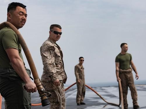 Marines, aboard the amphibious assault ship Bataan (LHD 5), scrub the flight deck, Feb. 20, 2020. (Mass Communication Specialist Seaman Apprentice Darren Newell/Navy)
