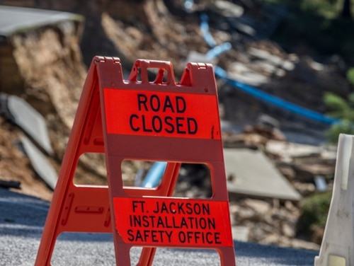 After two days of a historic amount of rainfall totaling 24 inches, Fort Jackson, S.C., sought to get back to business as usual. Here a simple traffic sign warns oncoming vehicular traffic of a massive crater in the road after the rains washed away the Semmes Lake dam located at the corner of Essayons and Semmes leaving the lake empty and the muddy bottom exposed. A handful of ducks and and a few onlookers were the only visible signs of life in the lake area. (U.S. Army photo by Sgt. 1st Class Brian Hamilton)