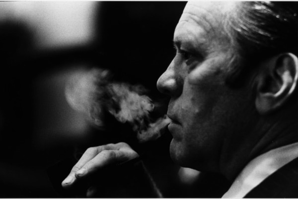 President Gerald Ford smokes his pipe at the National Security Council meeting on April 28, 1975, where it was decided to evacuate Saigon. (Ford Library)