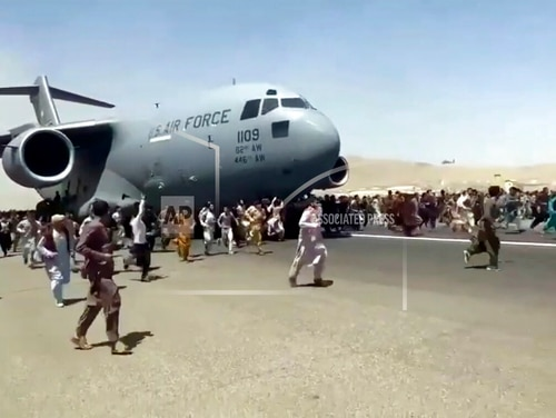 Hundreds of people run alongside a U.S. Air Force C-17 transport plane as it moves down a runway of the international airport, in Kabul, Afghanistan, Monday, Aug.16. 2021. Thousands of Afghans have rushed onto the tarmac at the airport, some so desperate to escape the Taliban capture of their country that they held onto the American military jet as it took off and plunged to death. (Verified UGC via AP)