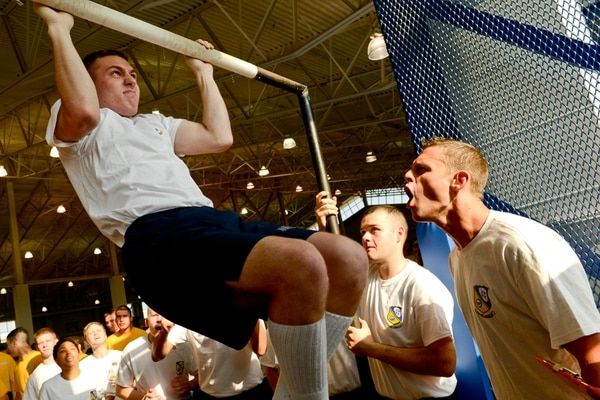 """140809-N-SH953-525 GREAT LAKES, Ill. (Aug. 9, 2014) Aviation Support Equipment Technician 1st Class Justin Kramer, Maintenance and Support team member of the U.S. Navy flight demonstration squadron, the Blue Angels, motivates a pull-up participant at Captain's Cup at Recruit Training Command (RTC) Great Lakes, Ill. Members of the Blue Angels went to RTC in support of Navy Recruit Division 940, the Blue Angels-sponsored division. The Recruit Division Sponsorship Program allows Navy commands to interact with recruits during training and take part in the """"Sailorization"""" process of turning individuals into well-rounded members of the U.S. Navy – making civilians into Sailors. (U.S. Navy photo by Mass Communication Specialist 2nd Class Kathryn E. Macdonald/Released)"""