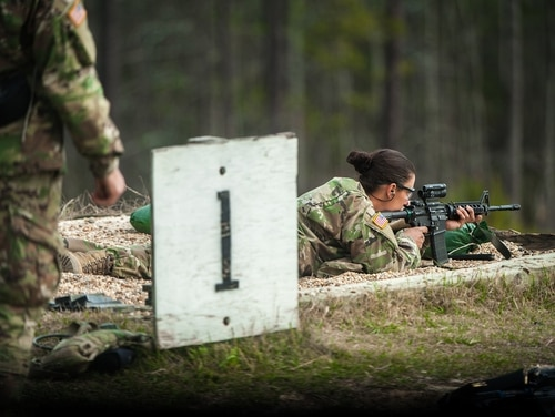 One of the first women to enlist into the infantry practices rifle marksmanship during one-station unit training. (Patrick A. Albright/Army)