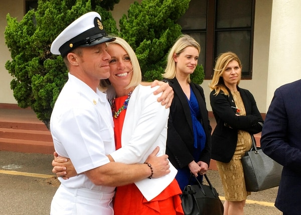"Special Warfare Operator Chief Edward ""Eddie"" Gallagher , left, hugs his wife, Andrea, after leaving a military courtroom on Naval Base San Diego on Thursday. (Julie Watson/AP)"