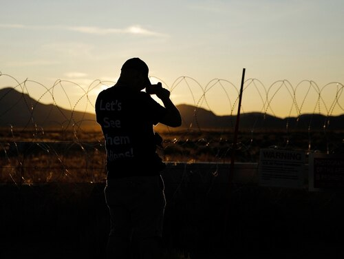 A man takes a picture of signs and razor wire near an entrance to the Nevada Test and Training Range near Area 51, Friday, Sept. 20, 2019, near Rachel, Nev. People came to visit the gate inspired by the