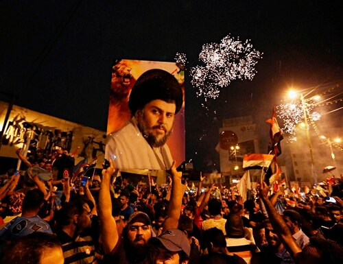 Supporters of Shia cleric Muqtada al-Sadr carry his image as they celebrate in Tahrir Square, in Iraq in May 2018. (Hadi Mizban/AP)