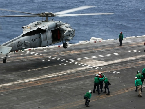 An MH-60S Sea Hawk helicopter from the Nightdippers of Helicopter Sea Combat Squadron 5 lands on the flight deck of the aircraft carrier Abraham Lincoln on July 8 while the warship was sailing the Arabian Sea. (Mass Communication Specialist Seaman Tristan Kyle Labuguen/Navy)