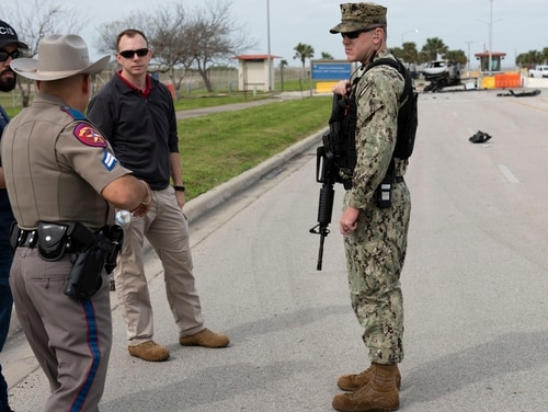 U.S. Navy Security Forces, Naval Criminal Investigative Service, and Texas Department of Safety personnel discuss details of an investigation after a vehicle unlawfully entered the base on Thursday morning. Navy Security Forces personnel opened fire after the suspect crashed his vehicle into a barrier and charged Security Forces personnel. No personnel were injured during the incident and emergency services pronounced the suspect deceased on the scene. (Anne Owens/Navy)