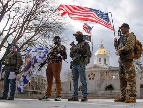 Several armed protesters stand in front of the New Hampshire Statehouse Sunday, Jan. 17, 2021, in Concord, N.H. (AP Photo/Winslow Townson)