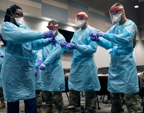 Members of the Florida National Guard (FLNG) gather with local hospital staff to collaborate on donning and doffing personal protective equipment (PPE) during Task Force – Medicals' response to the COVID-19 virus, March 17, 2020. The FLNG is mobilizing up to 500 Citizen-Soldiers and Airmen in support of the Florida Department of Health response in Broward County. (Sgt. Leia Tascarini/Army)