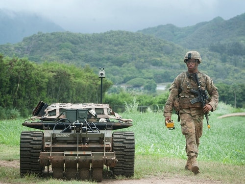 A U.S. Army Pacific soldier moves down a road while controlling an unmanned vehicle as part of the Pacific Manned Unmanned–Initiative July 22, 2016, at Marine Corps Training Area Bellows, Hawaii. (Staff Sgt. Christopher Hubenthal/Air Force)