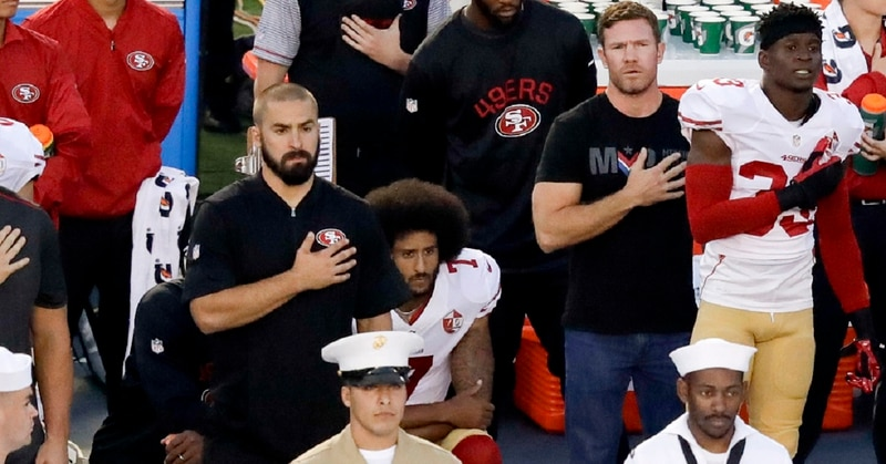 Army veteran Nate Boyer stands to the right of San Francisco 49ers quarterback Colin Kaepernick, middle, before a Sept. 1, 2016, preseason game in San Diego. (Chris Carlson/AP)