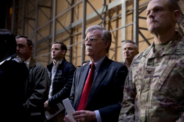 National security adviser John Bolton, center, listens as President Donald Trump speaks at a hanger rally at Al Asad Air Base, Iraq, Wednesday, Dec. 26, 2018. In a surprise trip to Iraq, President Donald Trump on Wednesday defended his decision to withdraw U.S. forces from Syria where they have been helping battle Islamic State militants. (Andrew Harnik/AP)
