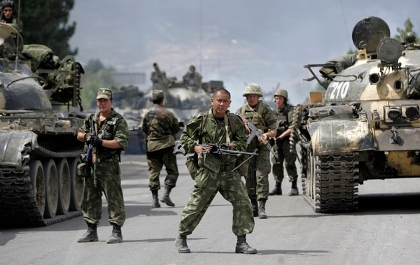 In this photo taken on Thursday, Aug. 14, 2008, Russian soldiers block the road on the outskirts of Gori, northwest of the capital Tbilisi, Georgia. Russia's Prime Minister Dmitry Medvedev in an interview broadcast by Russian state television Tuesday Aug. 7, 2018, on the 10th anniversary of the Russia-Georgia war, issued a stern warning that incorporating Georgia into NATO could trigger a new