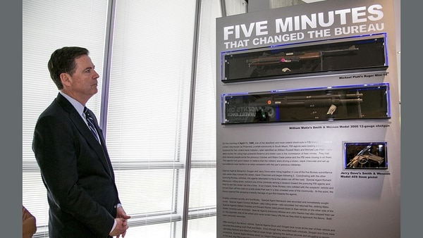 "FBI director James Comey unveils a three-panel memorial display that tells the story of the ""1986 FBI Miami Shootout."" It was this gun battle that spawned the .40S&W round and decades of debate over which round is best. (Photo FBI)"