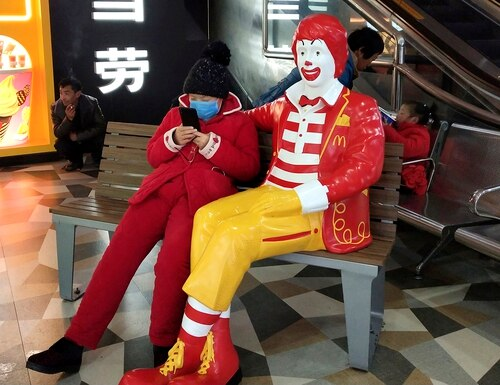 A woman wears a face mask and she uses her smartphone as she sits next to a statue of Ronald McDonald at a restaurant in Suzhou in eastern China's Jiangsu Province on Sunday. A new viral illness being watched with a wary eye around the globe accelerated its spread in China on Sunday with 56 deaths so far. (Chinatopix via AP)