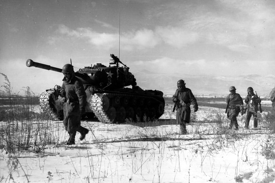 A column of troops and armor of the 1st Marine Division move through communist Chinese lines during their successful breakout from the Chosin Reservoir in North Korea. (Marine Corps)