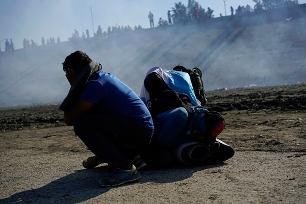 Three Honduran migrants huddle in the riverbank amid tear gas fired by U.S. agents on the Mexico-U.S. border after they and a group of migrants got past Mexican police at the Chaparral border crossing in Tijuana, Mexico, Sunday, Nov. 25, 2018. (Ramon Espinosa/Associated Press)