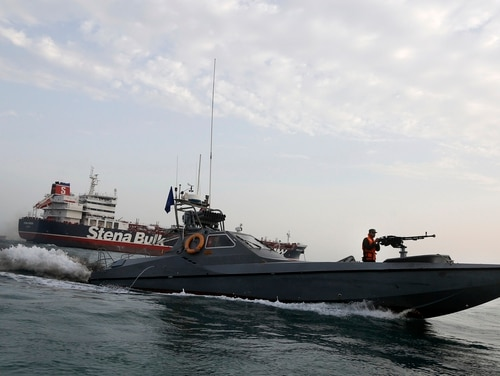 On July 21 a speedboat belonging to Iran's Revolutionary Guard zips around a British-flagged oil tanker, the Stena Impero, which was seized by the Guard, in the Iranian port of Bandar Abbas. T (Hasan Shirvani/Mizan News Agency via AP)