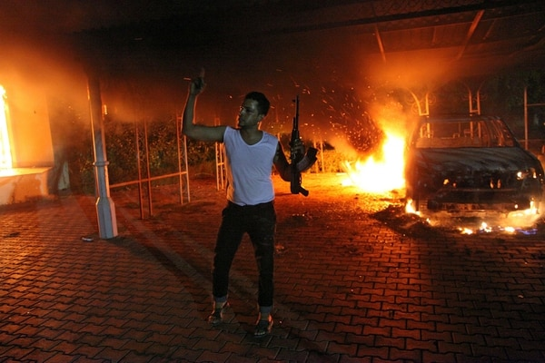 An armed man waves his rifle as buildings and cars are engulfed in flames after being set on fire inside the US consulate compound in Benghazi late on September 11, 2012. An armed mob protesting over a film they said offended Islam, attacked the US consulate in Benghazi and set fire to the building, killing one American, witnesses and officials said. AFP PHOTO