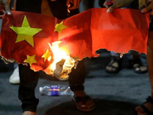 In this Nov. 20 photo, students burn a Chinese flag as they protest against the visit of Chinese President Xi Jinping outside the Presidential palace in Manila. The Philippine foreign secretary has ordered the filing of a diplomatic protest against China after Chinese coast guard ships reportedly strayed near a Philippine-occupied shoal in the disputed South China Sea. (Aaron Favila/AP)