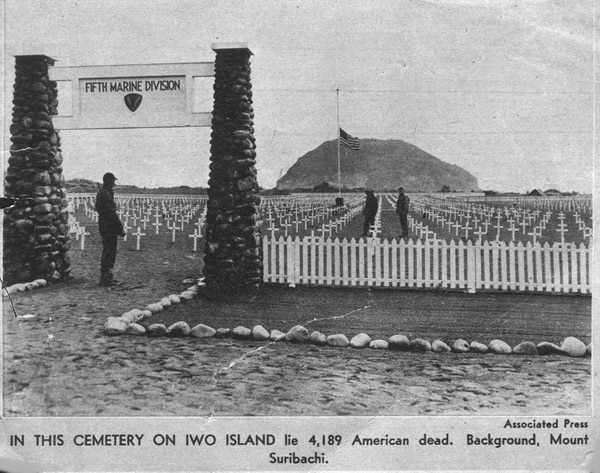 A clipping showing a cemetery dedicated to the Fifth Marine Division on Iwo Jima, with Mt. Suribachi looming in the background. (AP)