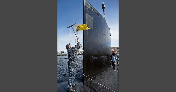 In this Thursday, March 15, 2018 photo, Senior Chief Petty Officer Carl Shafer untangles the halyards on the gaff during preparations for the commissioning of the U.S. Navy Virginia-class attack submarine PCU (pre-commissioning unit) Colorado (SSN 788) at the naval submarine base, Thursday, March 15, 2018, in Groton, Conn. (Sean D. Elliot/The Day via AP)