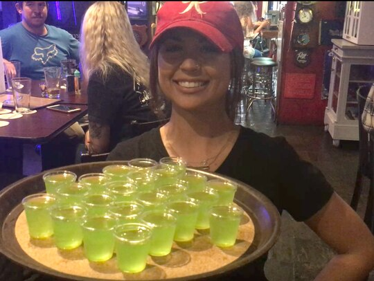 Ashley Brenner, a waitress at the Horse & Cow in Bremerton, Washington, hands out shots of the bar's