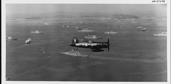 A Vought F4U-4B Corsair from Fighter Squadron 113 (VF-113) off the aircraft carrier Philippine Sea (CV-47), flies a combat air patrol over U.S. warships and U.N. shipping in Inchon anchorage, South Korea, 2 October 1950. Wolmi-Do island is in the right center distance, with Inchon city beyond to the right. The battleship Missouri is immediately below the Corsair. (U.S. Naval History and Heritage Command)