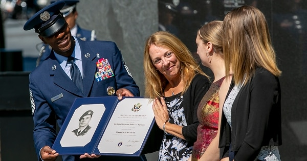 Chief Master Sgt. of the Air Force Kaleth Wright presents Valerie Nessel and Brianna and Madison Chapman, John Chapman's wife and daughters, with a letter of promotion raising Chapman's rank to master sergeant during a Medal of Honor ceremony at the Air Force Memorial Aug. 24. (Alan Lessig/Staff)