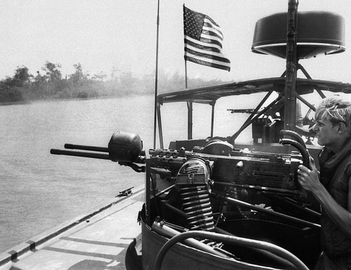 A Navy seaman fires twin machine guns of a PBR (Patrol Boat River) into the free-fire zone on the shoreline along the Mekong Delta southwest of Saigon, February 1969. Navy boats would often fire into the area in case Viet Cong troops were concealed in the canals of the Delta. (AP Photo)