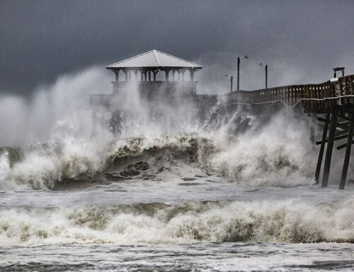 Waves slam the Oceana Pier & Pier House Restaurant in Atlantic Beach, N.C., Sept. 13, 2018, as Hurricane Florence approaches the area. (Travis Long /The News & Observer via AP)