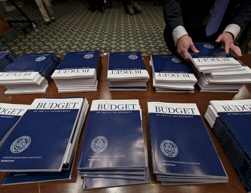 Copies of the proposed fiscal 2015 budget are stacked on a table in a congressional hearing room on March 4, 2014. (J. Scott Applewhite/AP)