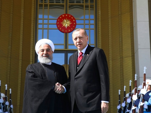 Turkey's President Recep Tayyip Erdogan, right, and Iran's President Hassan Rouhani shake hands during a welcome ceremony in Ankara, Turkey, Wednesday, April 4, 2018. The leaders of Russia, Iran and Turkey are meeting in the Turkish capital for talks on Syria's future. The leaders are expected to reaffirm their commitment to Syria's territorial integrity and the continuation of local cease-fires when they meet Wednesday. (Kayhan Ozer/pool photo via AP)