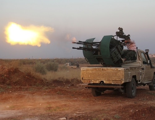 Rebel fighters fire a heavy machine gun during clashes with Syrian pro-government forces on the frontline facing Deir al-Zoghb, a government-held area in the northwestern Idlib province, on August 31, 2015. AFP PHOTO / OMAR HAJ KADOUR (Photo credit should read OMAR HAJ KADOUR/AFP/Getty Images)