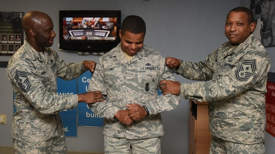 Newly minted Technical Sgt. Courtney Hill of the 81st Security Forces Squadron at Keesler Air Force Base has his new stripes tacked on in a Stripes for Exceptional Performers promotion ceremony in March 2017. The Air Force this month selected 8,416 staff sergeants for promotion to E-6. (Kemberly Groue/Air Force)