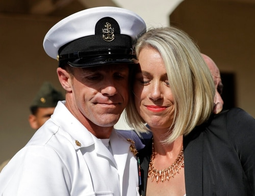 """Special Warfare Operator Chief Edward """"Eddie"""" Gallagher, left, and his wife Andrea hug after leaving the Naval Base San Diego courthouse after a July court-martial plagued by allegations of police and prosecutorial misconduct. In the wake of the Gallagher case, senior Navy leaders sparked a probe into the Navy's legal community. (Gregory Bull/AP)"""