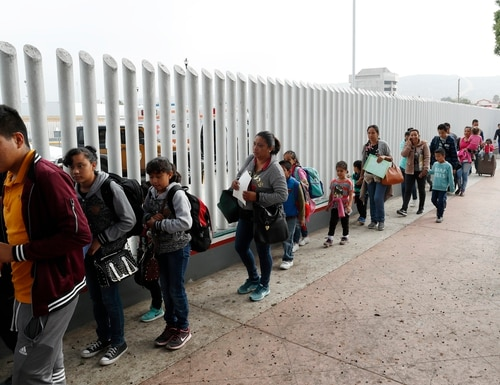 People line up to cross into the United States on July 26, 2018, to begin the process of applying for asylum near the San Ysidro port of entry in Tijuana, Mexico. (Gregory Bull/AP)
