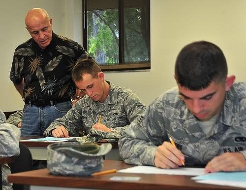 A test control officer at Tyndall Air Force Base helps airmen understand what they need to fill out on the tests they take for promotion in 2014. (A1C Sergio Gamboa/Air Force)